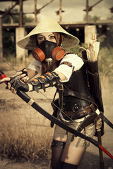 Attractive woman warrior in the mask holding in her hands bow an