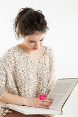 Brunette in knitted pullover sitting and reading a book