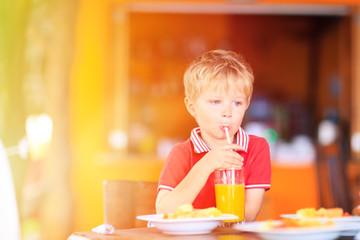 cute little boy drinking juice in cafe