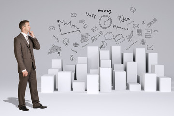 Businessman in suit thinks. Many white cubes with business