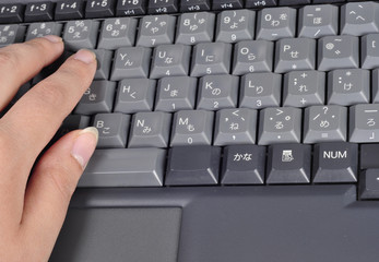 computer keyboard with Japanese characters and hand