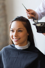 happy woman with stylist coloring hair at salon