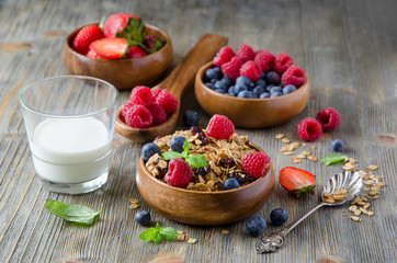 Fresh healthy breakfast with granola and berries, wooden backgro