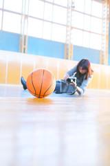 Woman photographing a basketball ball