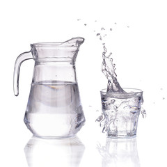 Fresh water glass with splash and bottle isolated