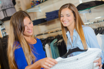 Two female friends clothes shopping