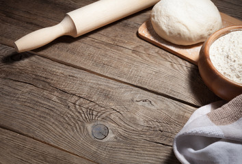 dough, flour and rolling pin on an old board.