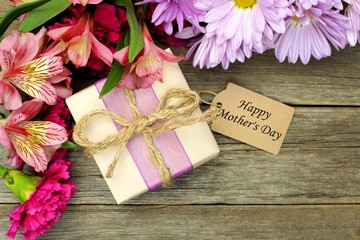 Flowers with gift box and Mother's Day tag on wood background