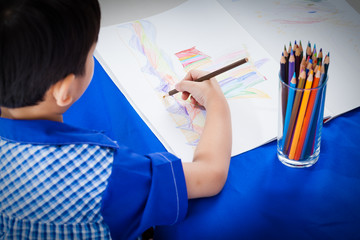 Little asian boy sitting at the table and drawing by colour penc