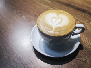 Cup of coffee with heart shape milk foam on wooden table backgro