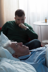 Ill father lying in hospital bed