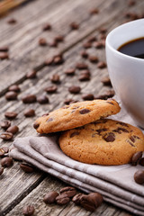 Tasty cookies and coffee cup on a wooden table.
