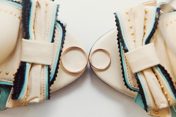 Two gold rings laying on woman shoes