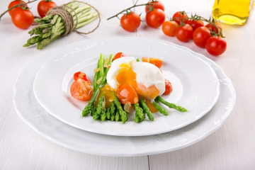 Green asparagus stems with soft-boiled egg, tomato and sauce.