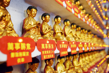 Different small golden Buddha statues in the interior of the Ten