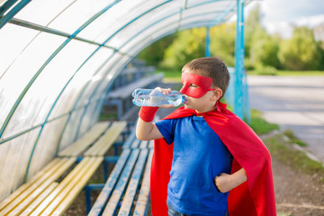 Superhero standing under canopy and drinking water from a bottle