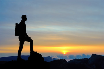 Silhouette of man at the top of the mountain on sunset