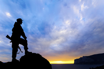 Silhouette of military soldier officer with weapons at sunset.