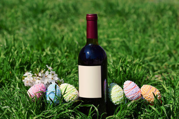 Wall Mural - Row of Easter eggs red wine bottle in Fresh Green Grass