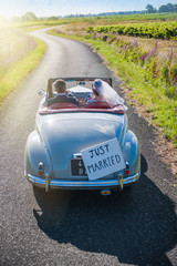 A newlywed couple is driving a retro car