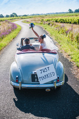 Top view, a newlywed couple is driving a retro car