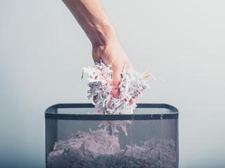 Hand putting shredded paper in basket