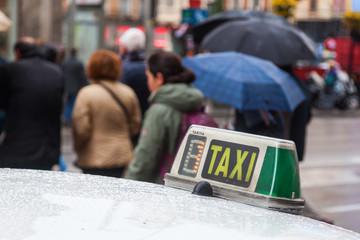 Taxischild mit Menschen im unscharfen Hintergrund