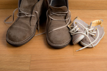 Closeup of father's shoes close to child's shoes on a parquet fl