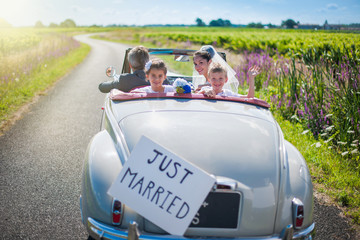 A newlywed couple is driving a retro car with their kids, rear v
