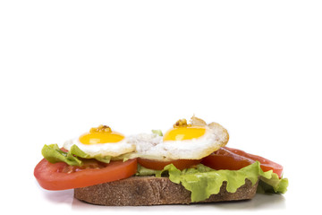 fried eggs with a little tomato and lettuce on a piece of fresh