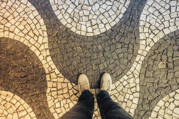 Light Sneakers shoes walking on Copacabana mosaic sidewalk top view, Rio de Janeiro