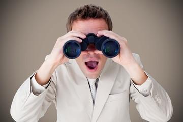 Composite image of positive businessman using binoculars