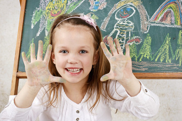 Happy child drawing with chalk on the blackboard