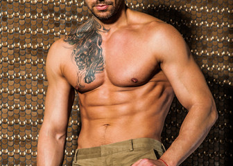 Handsome muscular man posing against goldt elegant background