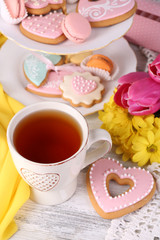 Composition of spring flowers, tea and cookies on table