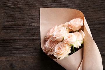 Bouquet of beautiful fresh roses wrapped in paper