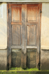 Ruined wooden door on cement wall