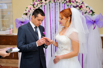 Groom putting ring on bride's finger under the arch