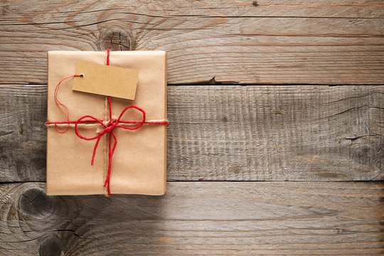 Gift box with tag on wooden background
