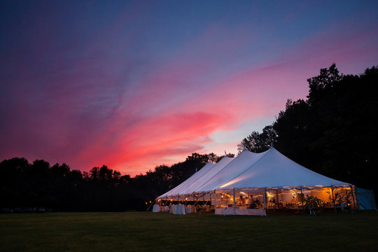 An event tent at night with a sunset during a wedding