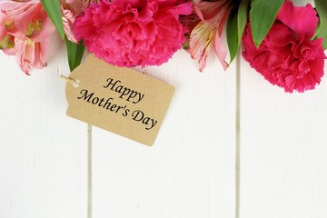 Mother's Day gift tag amongst pink flowers against white wood