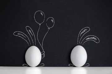 Two Easter eggs with painted Easter Bunny on the blackboard