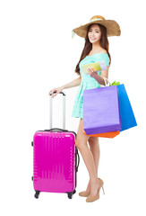 young woman holding shopping bags and travel suitcase