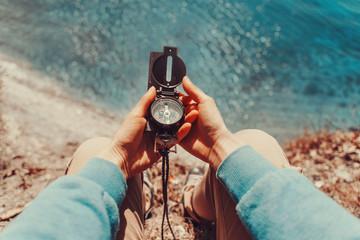 Traveler holding a compass on coastline