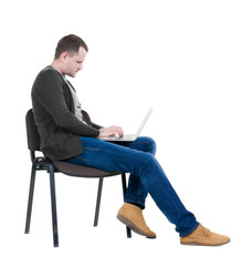 Side view of a man sitting on a chair to study with a laptop.
