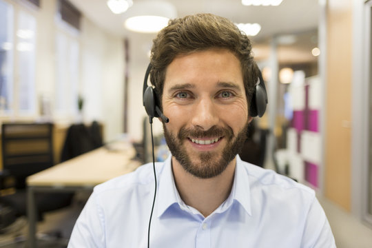 Cheerful Businessman in the office on video conference, headset,
