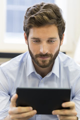 Casual business man working on tablet computer in office