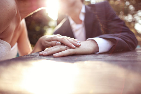 Holding hands with wedding ring in the sunlight