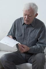 Aged man reading unpaid bill