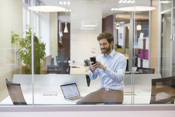 Hipster casual man.Typing text message on mobile phone in office